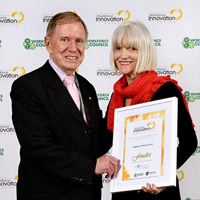 Photo of former Australian High Court Justice Michael Kirby presenting Finalist Certificate to Linda Harnett, at the Workforce Council Innovation Awards